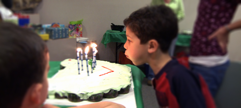 Kid blowing out birthday candles